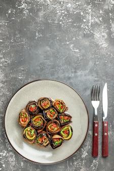Bovenaanzicht gevulde auberginebroodjes op witte ovale plaatvork en mes op grijs oppervlak