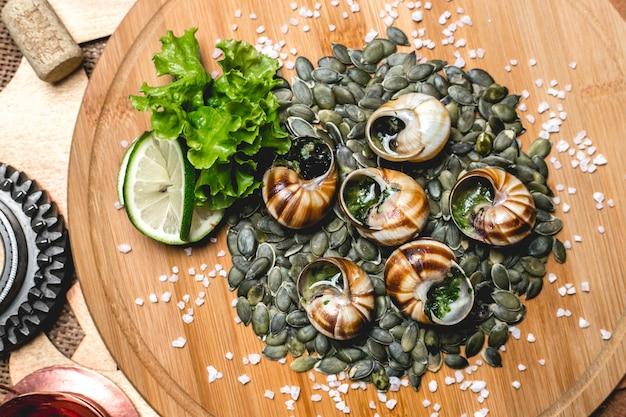 Bovenaanzicht gevulde slakken op pompoenpitten met plakjes limoen