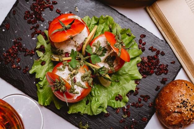 Bovenaanzicht gevulde tomaten met saus op een blad van sla met gesneden ‹citroen en gedroogde berberis