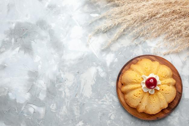 Bovenaanzicht gewone cake met room en kers op het lichte bureau koekje bak cake suiker zoet