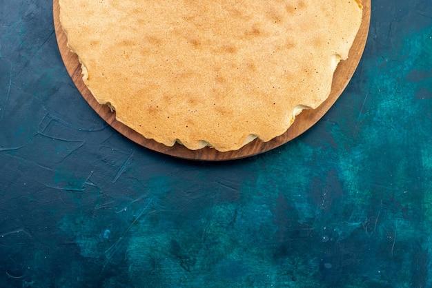 Bovenaanzicht gewoon cakedeeg gebakken rond gevormd op donkerblauw bureau