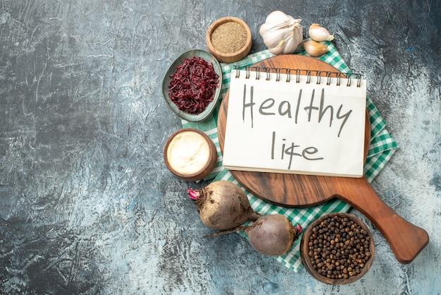 Bovenaanzicht gezond leven geschreven op notitieblok op houten bord kruiden in kommen knoflookbieten op grijze tafel