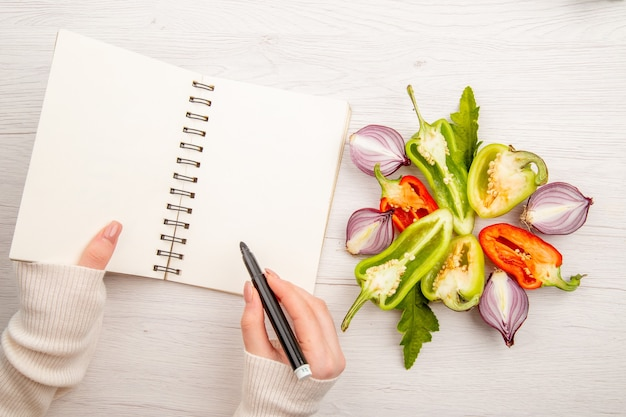 Bovenaanzicht gezond leven schrijven door vrouw met groenten op wit bureau