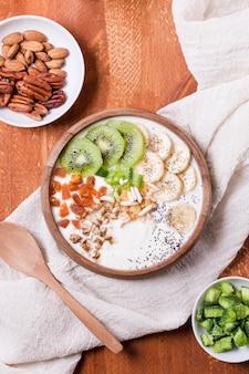 Bovenaanzicht gezond ontbijt kom met yoghurt en fruit