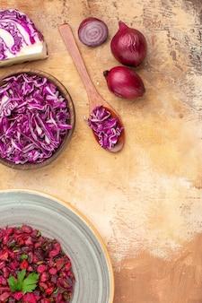 Bovenaanzicht gezonde bietensalade in een grijze plaat gemaakt van rode uien en een kom gehakte rode kool en op een houten ondergrond met kopieerplaats