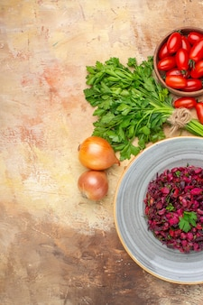 Bovenaanzicht gezonde bietensalade op een grijze plaat met verse groenten voor de bereiding op een houten ondergrond met vrije ruimte voor tekst