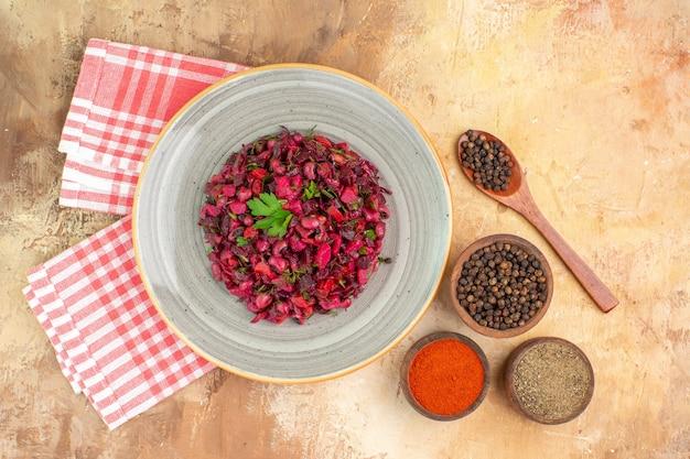 Bovenaanzicht gezonde groentesalade op een keramische plaat met een kom zwarte peper, kurkuma en gemalen zwarte peper op lichte houten achtergrond met kopieerruimte