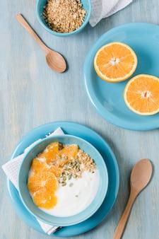 Bovenaanzicht gezonde ontbijtkom met sinaasappel