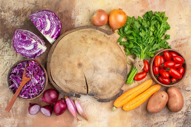 Bovenaanzicht gezonde salade ingrediënten gemaakt van een bosje rode kool peterselie roma tomaten wortel aardappelen en uien rond een snijplank op een houten tafel met kopieerruimte