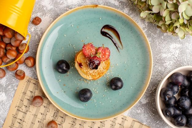 Bovenaanzicht gezouten chips ontworpen met aardbeien in plaat samen met sleedoorns op de witte tafel, chips snack fruitbes
