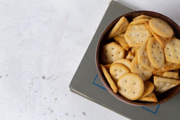 Bovenaanzicht gezouten crackers in bruine plaat op de lichte achtergrond cracker scherpe snack foto