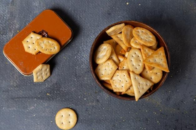 Bovenaanzicht gezouten crackers lekker en heerlijk op de donkere achtergrond snack knapperige cracker foto