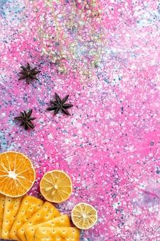 Bovenaanzicht gezouten crackers met citroen op roze bureau