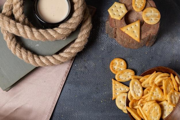 Bovenaanzicht gezouten lekkere chips met kopje melk op de grijze achtergrond voedsel ontbijt snack