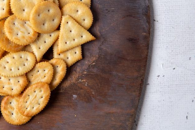 Bovenaanzicht gezouten smakelijke chips op het houten bureau en lichte achtergrond scherpe cracker snack foto