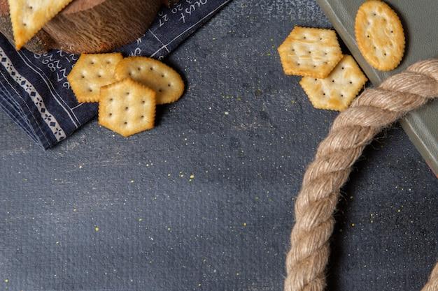 Bovenaanzicht gezouten smakelijke crackers met touwen op de grijze achtergrond cracker scherpe snack foto