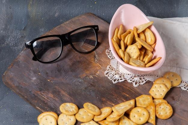 Bovenaanzicht gezouten smakelijke crackers met zonnebril op het houten bureau en grijze achtergrond snack scherpe cracker foto