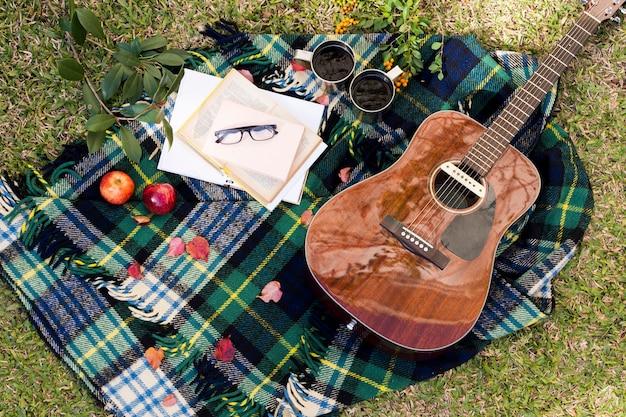 Bovenaanzicht gitaar op picknick doek