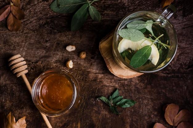 Bovenaanzicht glas met warm water en citroen met honing