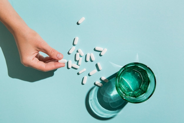 Bovenaanzicht glas met water en medicijnen op tafel