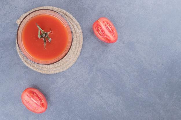 Bovenaanzicht. glas vers tomatensap en plakjes tomaat op een grijze achtergrond.