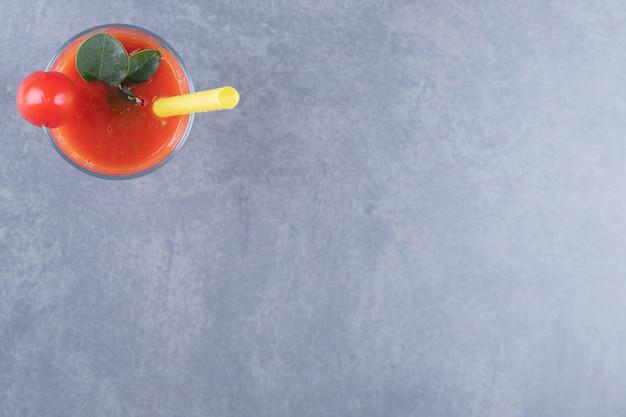 Bovenaanzicht. glas vers tomatensap en tomaten op een grijze achtergrond.