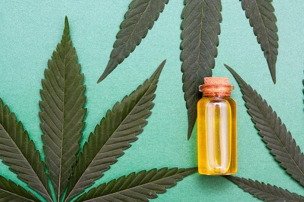 Bovenaanzicht glazen fles met wietolie in de buurt van plant