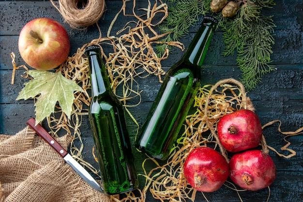 Bovenaanzicht glazen flessen met verse granaatappels op donkere achtergrond