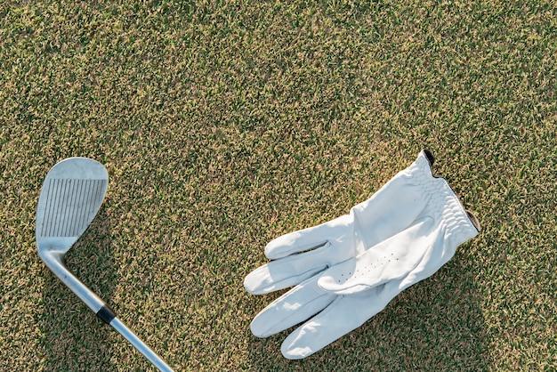 Bovenaanzicht golfclub en handschoen