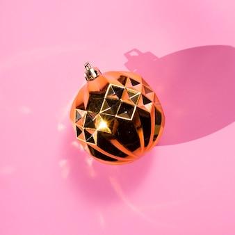 Bovenaanzicht gouden bol op roze achtergrond