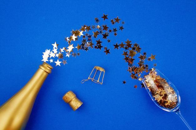 Bovenaanzicht gouden fles champagne, glas en confettie. feest, nieuwjaar, kerstviering