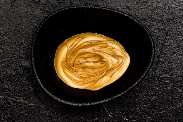 Bovenaanzicht gouden gesmolten verf in een zwarte kom