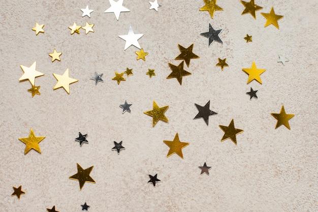 Bovenaanzicht gouden sterren in verschillende grootte op tafel