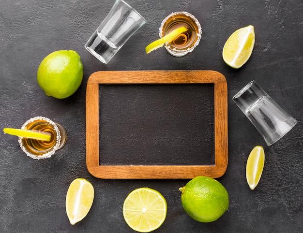 Bovenaanzicht gouden tequila shots en limoen met leeg bord