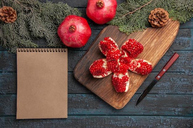 Bovenaanzicht granaatappel aan boord gepilde granaatappel op snijplank naast vuren takken met kegels mes en crème notebook op grijze ondergrond