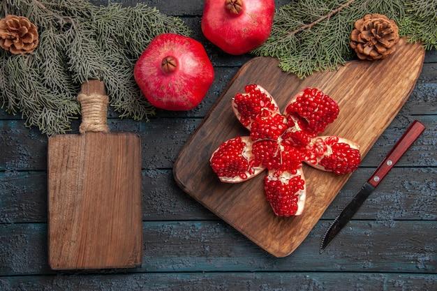 Bovenaanzicht granaatappel aan boord gepilde granaatappel op snijplank naast vuren takken met kegels mes en houten keukenbord op grijze ondergrond