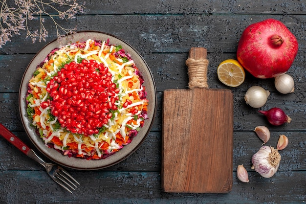 Bovenaanzicht granaatappel citroen knoflook snijplank tussen gepelde granaatappel knoflook ui citroen en bord schotel met vork op tafel