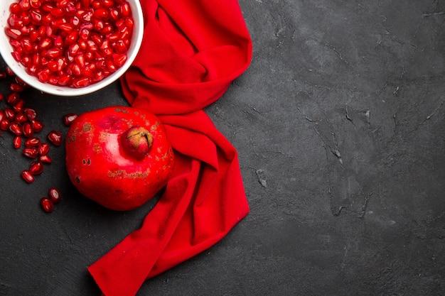 Bovenaanzicht granaatappel granaatappel naast de granaatappelpitjes in de kom rood tafelkleed