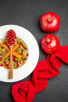 Bovenaanzicht granaatappel groente salade lepel met zaden van granaatappels tafelkleed