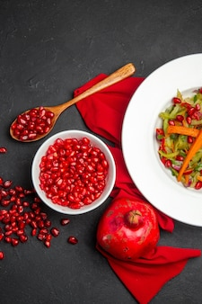 Bovenaanzicht granaatappel kom met zaden van granaatappel groente salade rood tafelkleed