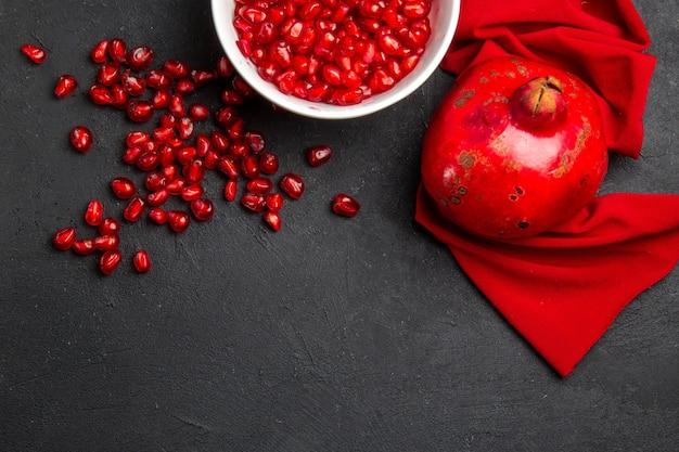 Bovenaanzicht granaatappel kom met zaden van granaatappel rood tafelkleed granaatappel