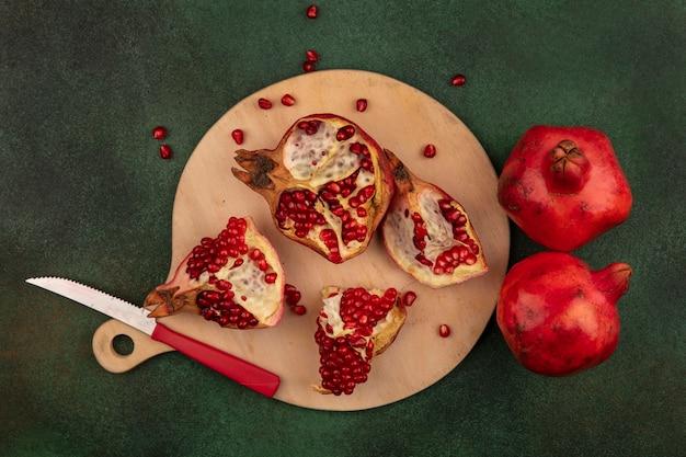 Bovenaanzicht granaatappel plakjes op snijplank met mes