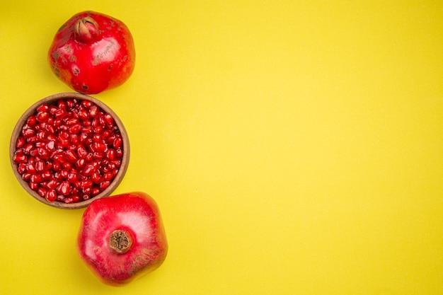 Bovenaanzicht granaatappel twee granaatappels en zaden van de smakelijke granaatappel in kom