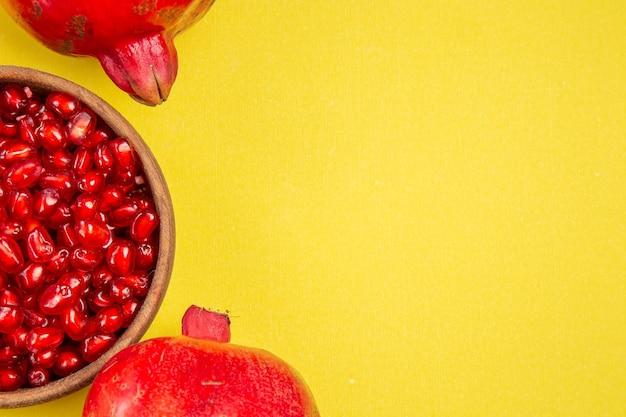 Bovenaanzicht granaatappel twee granaatappels kom met zaden van granaatappel op de gele tafel