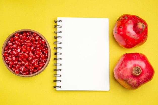 Bovenaanzicht granaatappel twee granaatappels wit notitieboekje kom met zaden van de smakelijke granaatappel