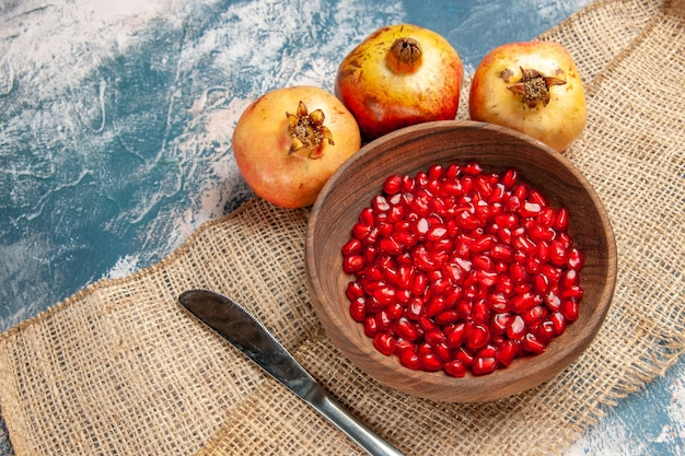 Bovenaanzicht granaatappel zaden in houten kom diner mes granaatappels op blauw-witte achtergrond