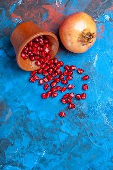 Bovenaanzicht granaatappel zaden in kleine houten kom een granaatappel op blauwe achtergrond met vrije ruimte