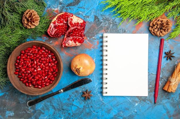Bovenaanzicht granaatappel zaden in kom diner mes een gesneden granaatappel dennenboom tak een notebook pen op blauwe ondergrond