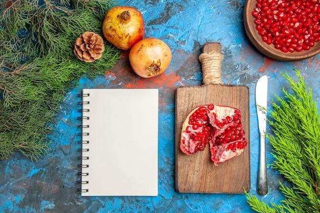 Bovenaanzicht granaatappel zaden in kom diner mes een gesneden granaatappel op snijplank een notitieboekje boomtakken op blauwe ondergrond