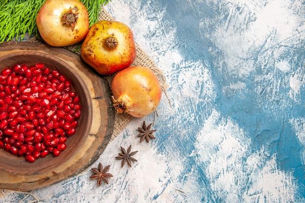 Bovenaanzicht granaatappel zaden in kom op boom houten bord kaneel anijs zaden granaatappels op blauw-wit oppervlak